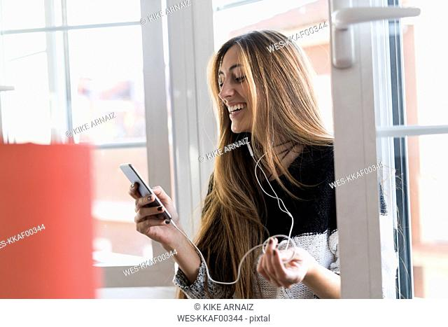 Happy young woman with cell phone and earphones at the window