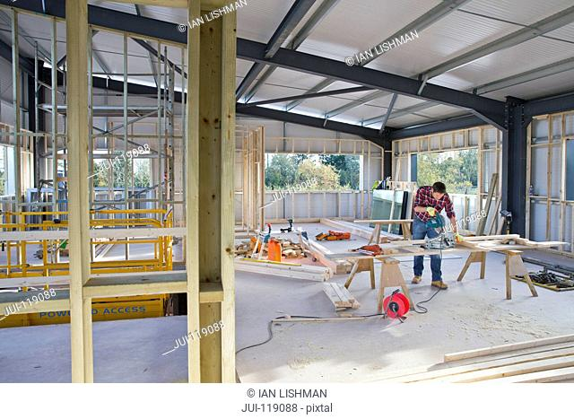 Building construction site interior with carpenter working in background