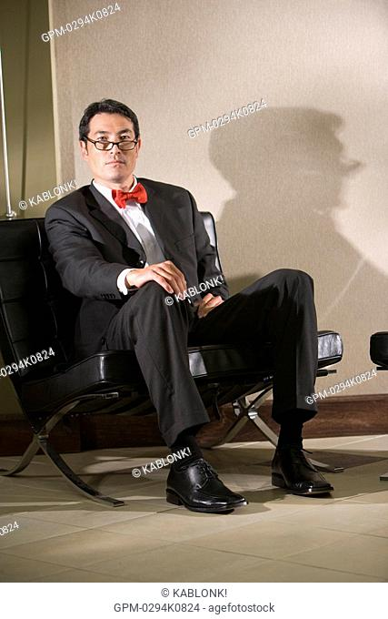 Close-up portrait of pensive Asian businessman sitting in modern lobby