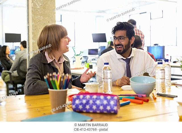 Laughing business people talking in office