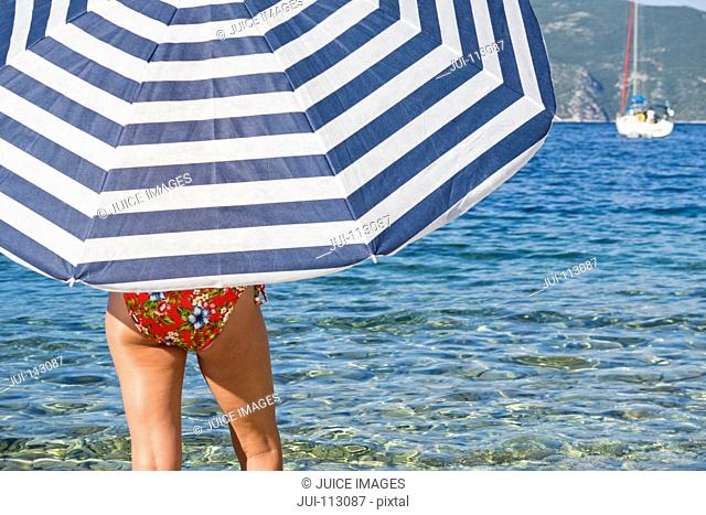 Woman in bikini under striped beach umbrella at ocean