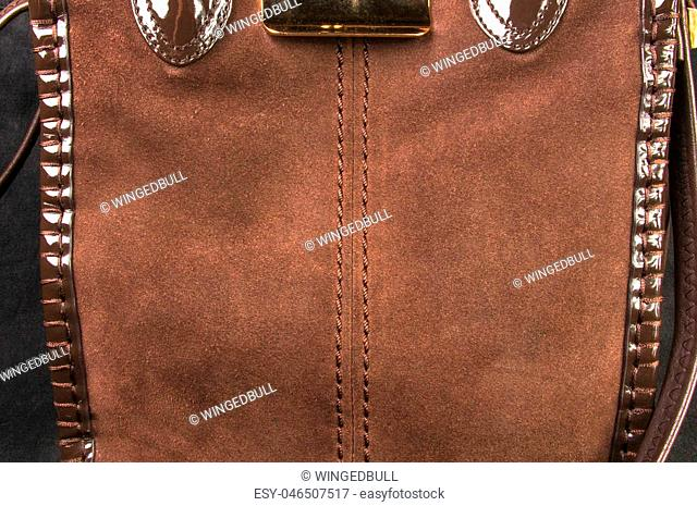 closeup of the fittings and seams on brown leather hand bag