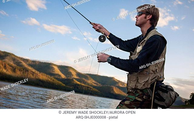 A young man in his early thirties fly fishing near Durango, Colorado