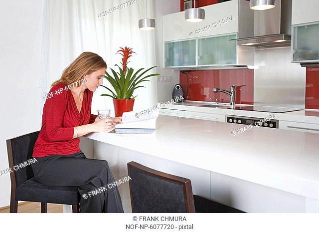 Woman sitting in modern kitchen interior