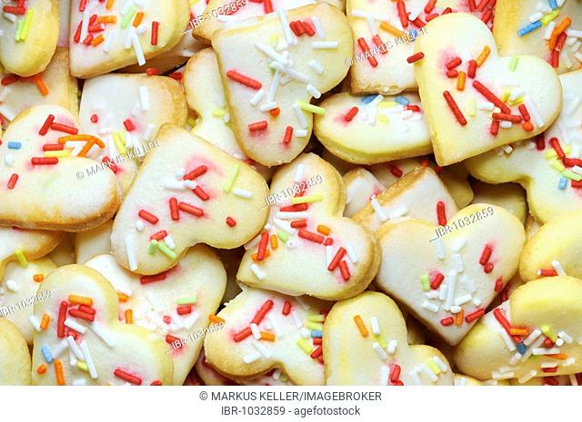 Heart-shaped short pastry biscuits with multicoloured sugar sprinkles, filling the picture