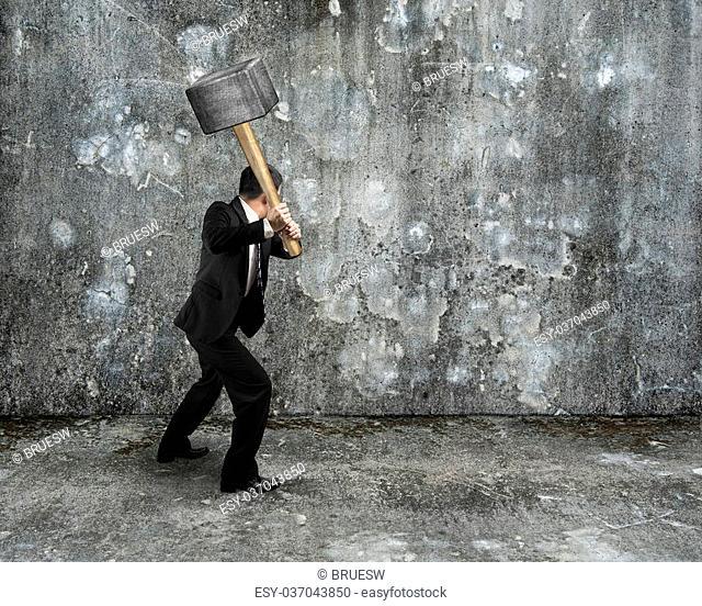 Businessman hold sledgehammer to crack old mottled concrete wall background