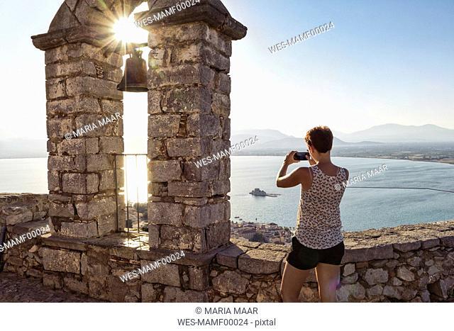 Greece, Peloponnese, Argolis, Nauplia, Argolic Gulf, woman photographing view from bell tower of Palamidi Fortress