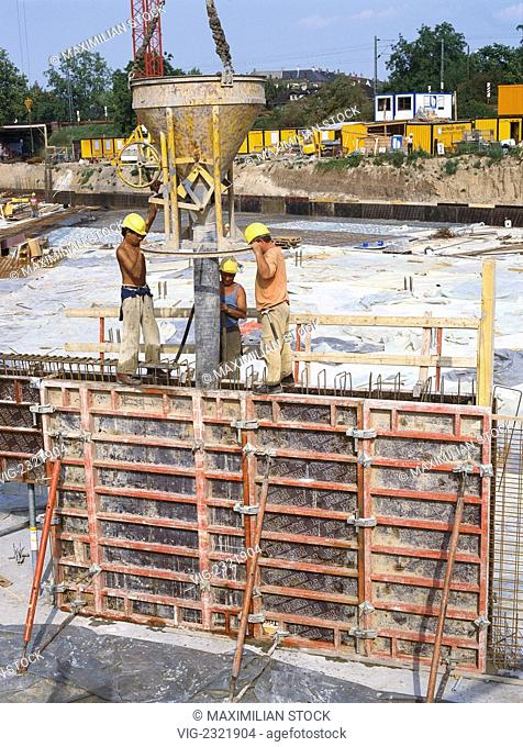 Building Site. Workers filling a steel reinforcement with concrete, - 01/01/2010