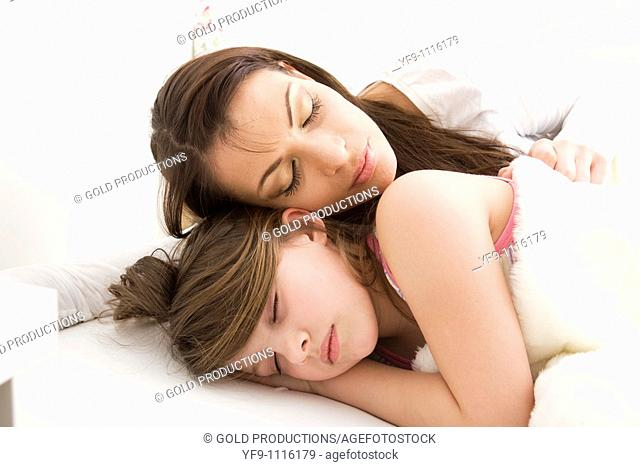 Mother and daughter sleeping in bed