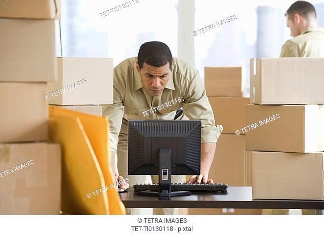 African delivery man looking at computer
