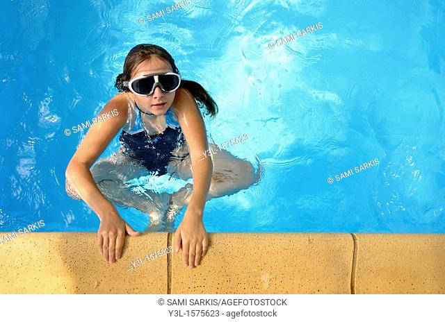 Girl 11 with goggles in swimming pool, Provence, France