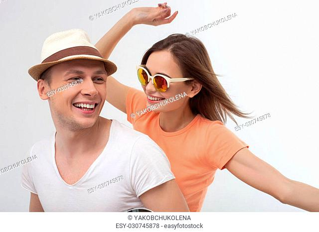 Cheerful young man and woman are making their trip together. The man is riding the motorbike with joy. His girlfriend is smiling happily. Isolated