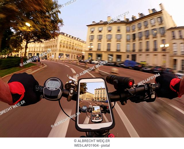 France, Versailles, Place Hoche, personal perspective of man riding e-bike at twilight