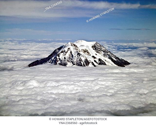 Mt. Rainier above the clouds. Rainier is the tallest mountain in th state of Washington about 55 miles southeast of Seattle. Mt