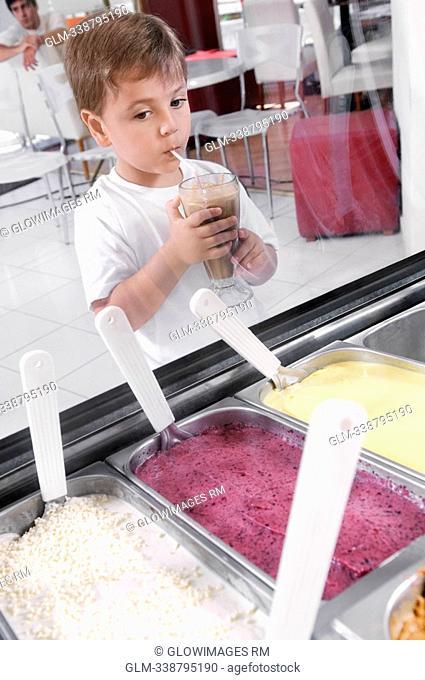 Boy looking at ice creams while drinking milkshake