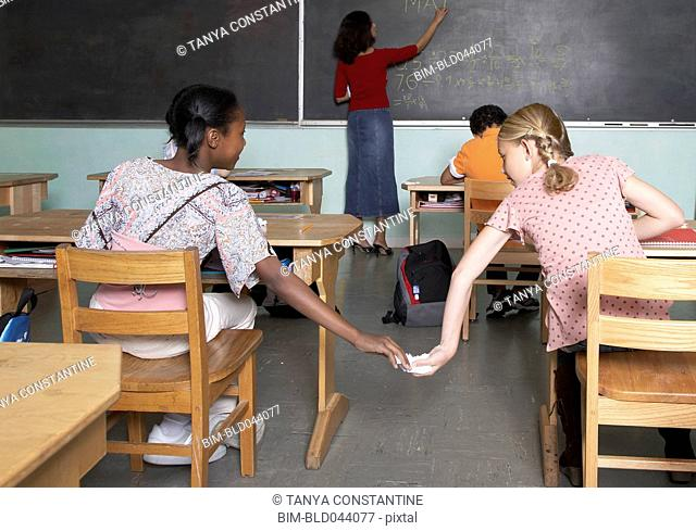 Multi-ethnic girls passing note in class