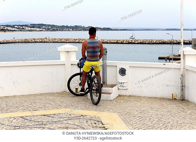 single young male tourist on a bicycle watching view for Meia Praia and mouth of the river Bensafrim and Atlantic Ocean, observing point near Batata beach