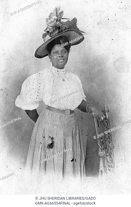 Three-quarter length portrait of an African American woman standing beside a chair, with one hand rested on the chair, wearing a checkered dress and a white...