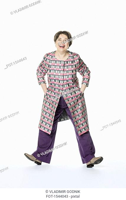Full length of happy woman standing with hands in pockets against white background