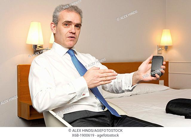 Business man sitting in hotel room in animated conversation