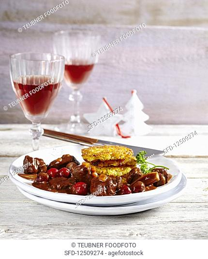 Wild boar goulash with cranberries and potato-sweet-potato fritters