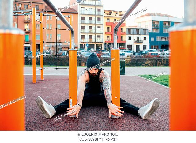 Man using parallel bars in outdoor gym