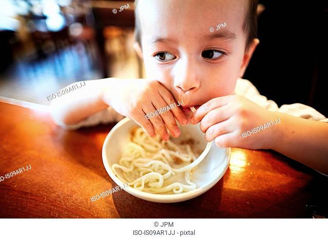 Boy eating noodles in restaurant