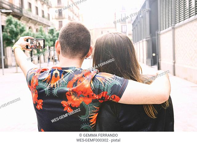 Spain, Barcelona, back view of couple taking a selfie with smartphone