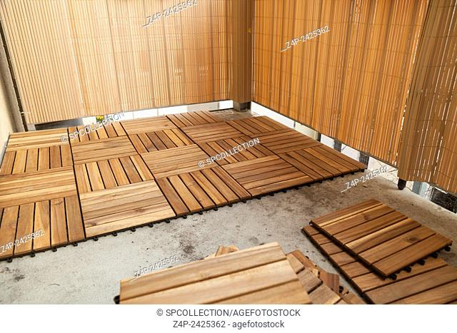 Lay wood tiles on floor of balcony