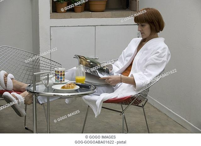 Woman relaxing at breakfast table