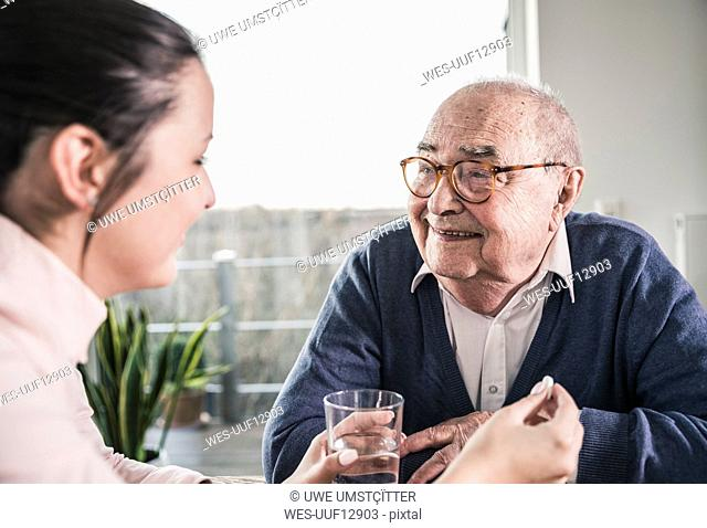 Woman holding pill and glass of water for smiling senior man