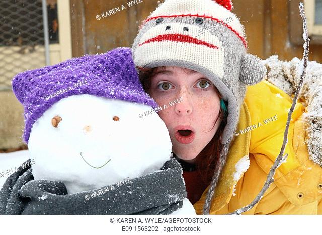 freckled girl in sock-monkey hat and yellow parka, standing with mouth open beside the snowman she built - snowman has purple hat, grey scarf