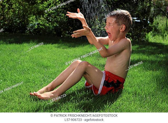 boy having shower outdoors, Switzerland