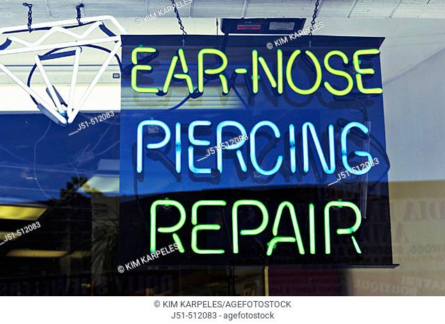 Neon sign in store window along Devon Avenue offering nose and ear piercing repair, multiethnic shopping district. Chicago. Illinois, USA