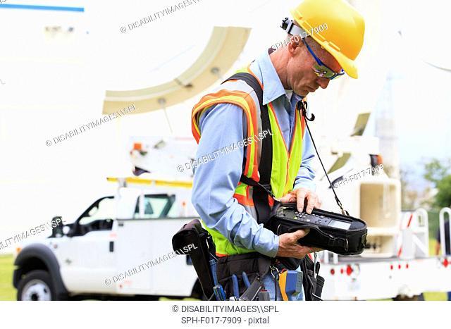 Communications engineer preparing measuring instrument for satellite antenna alignment