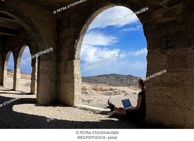 Spain, Tenerife, Abades, Sanatorio de Abona, woman sitting in ghost town building using laptop