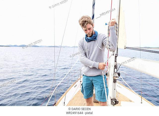 Young man on yacht curling up rope