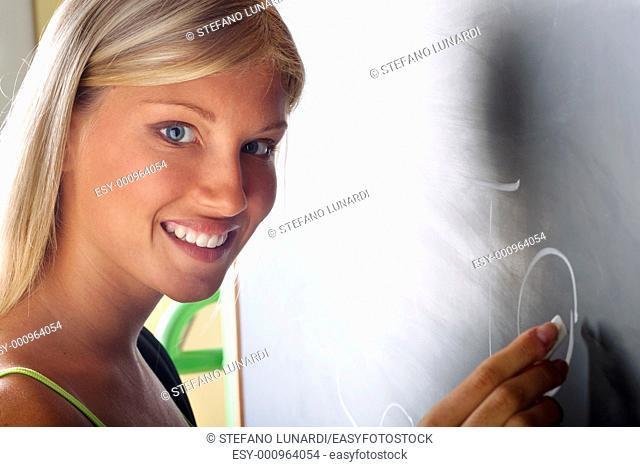 Happy student writing on blackboard