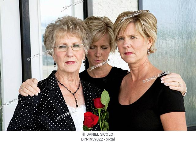 A Mother And Her Two Daughters Grieving A Death; Edmonton, Alberta, Canada