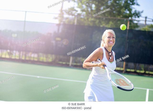 Smiling mature woman playing tennis
