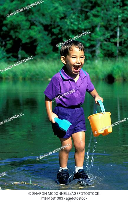 Afghan-American boy thrilled with water play in pond, summer, Midwest USA