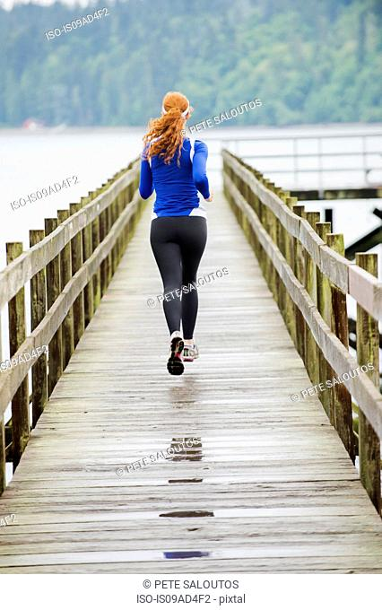 Teenage girl jogging on pier, Bainbridge Island, Washington, USA
