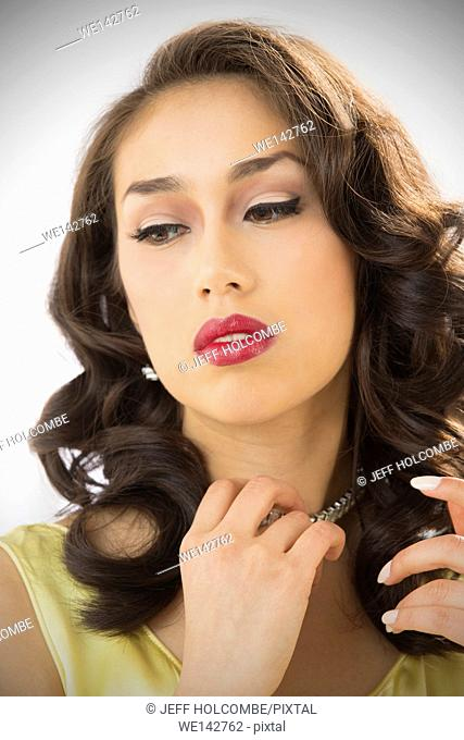 Beautiful young woman head and shoulders portrait in vintage yellow dress, with a thoughtful, glamorous look