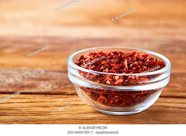 Transparent glass bowl with dried chilly on rustic wooden background, close-up, side view, shallow depth of field. Some copy space for your text