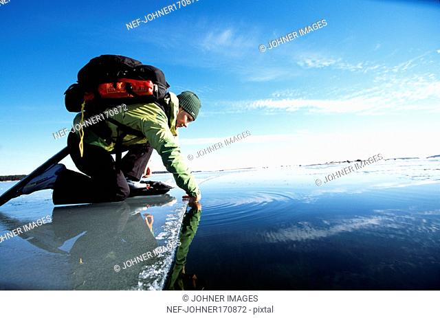 Woman with long-distance skates sitting on an ice floe