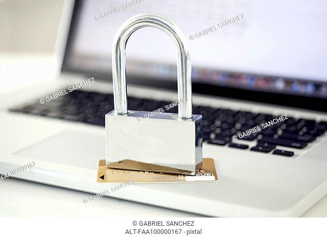 Padlock and credit card sitting on top of laptop computer