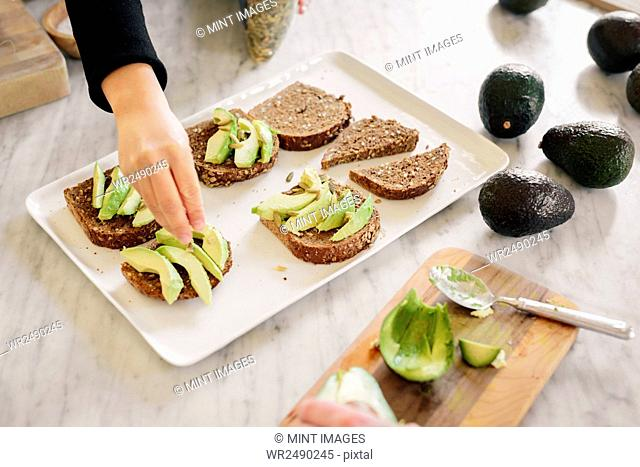 A woman preparing open sandwiches with brown bread and avocado