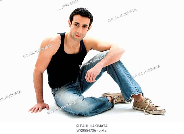 Handsome Caucasian guy wearing black tank top and jeans sitting on floor, isolated