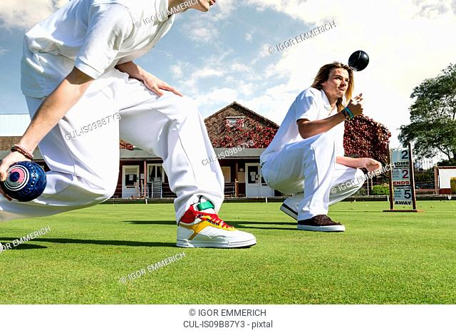 Cropped shot of two young men lawn bowling on bowling green