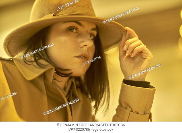 portrait of woman touching hat, indoors, thoughtful pensive emotion, in Munich, Germany